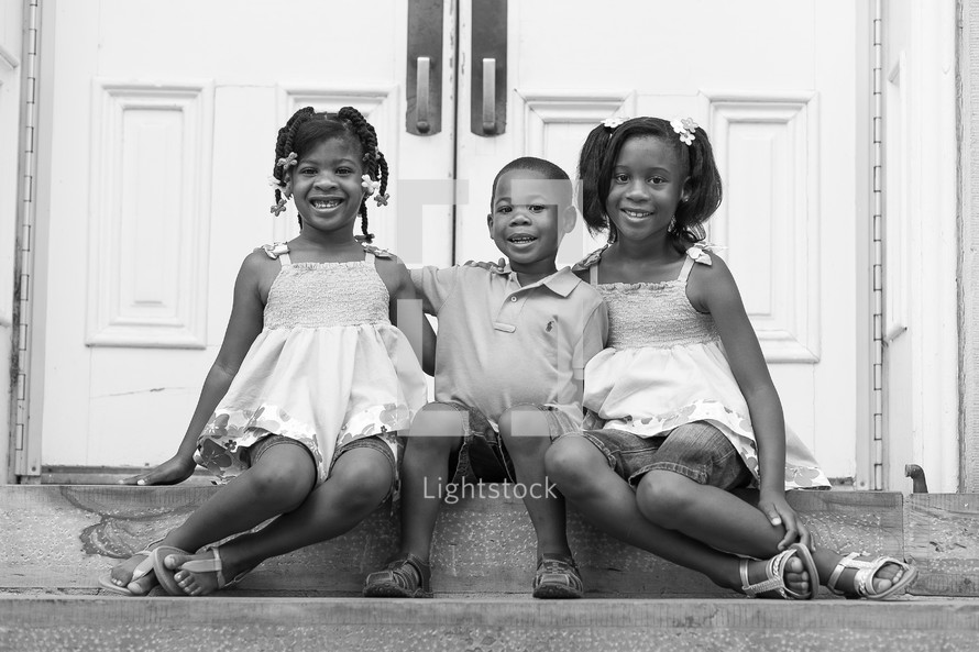 Smiling siblings sitting on a step.