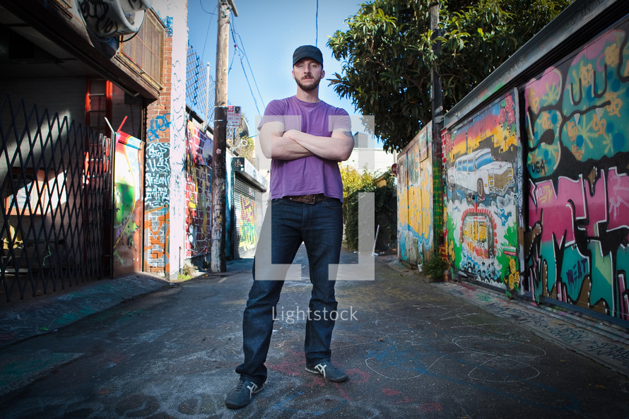 Man in jeans with purple shirt and baseball cap standing in grafitti-lined alley.