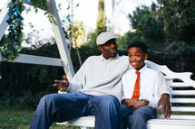 a father and son sitting on a swing