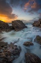tide washing onto rocks on a beach shore