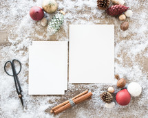 white paper and envelopes with ornaments in snow