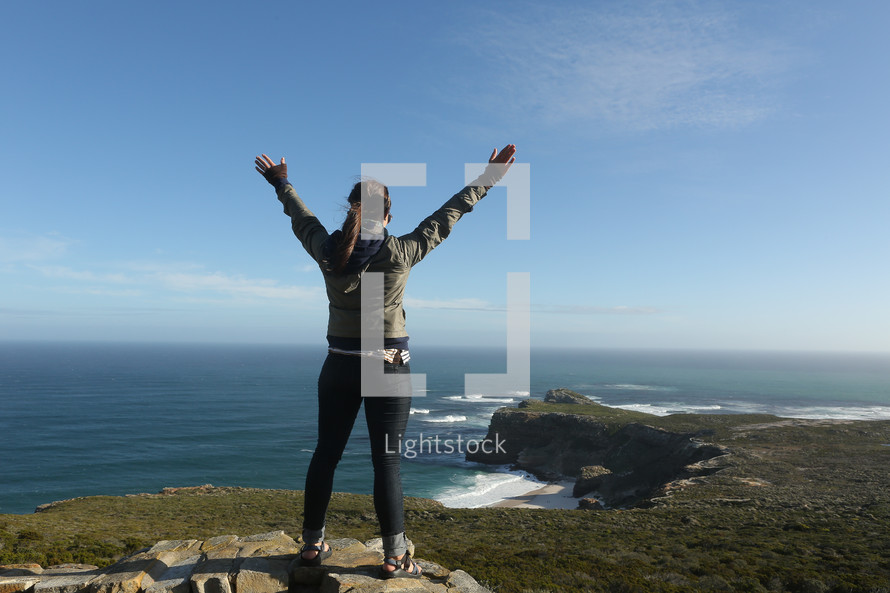 woman standing on a mountain top over the ocean with arms raised in praise and worship