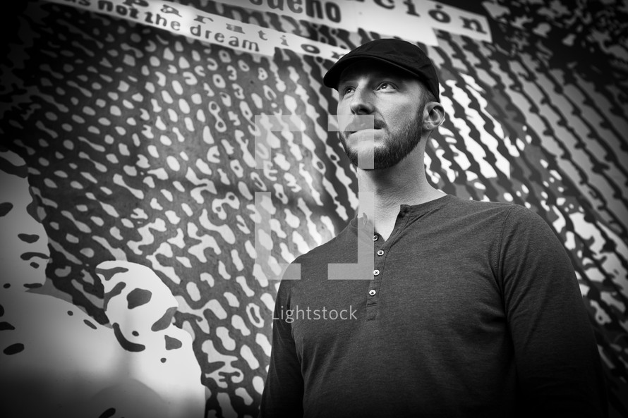 man standing in front of street art on a wall