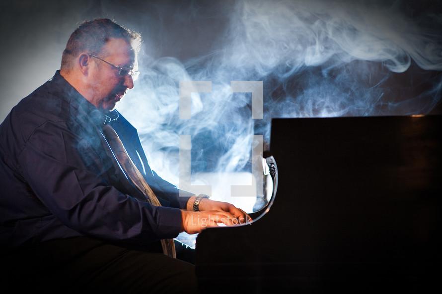 smoke over a man playing a piano