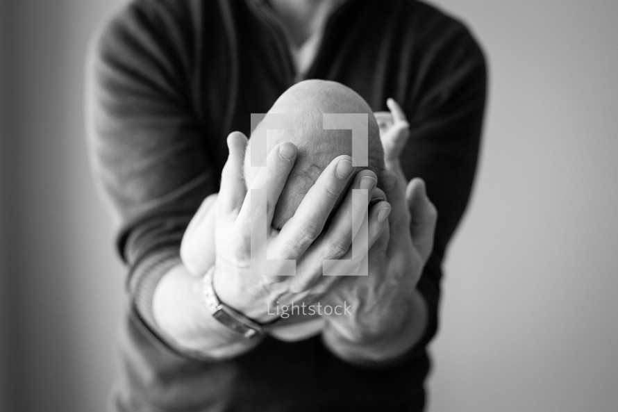 a father holding a newborn in his hands