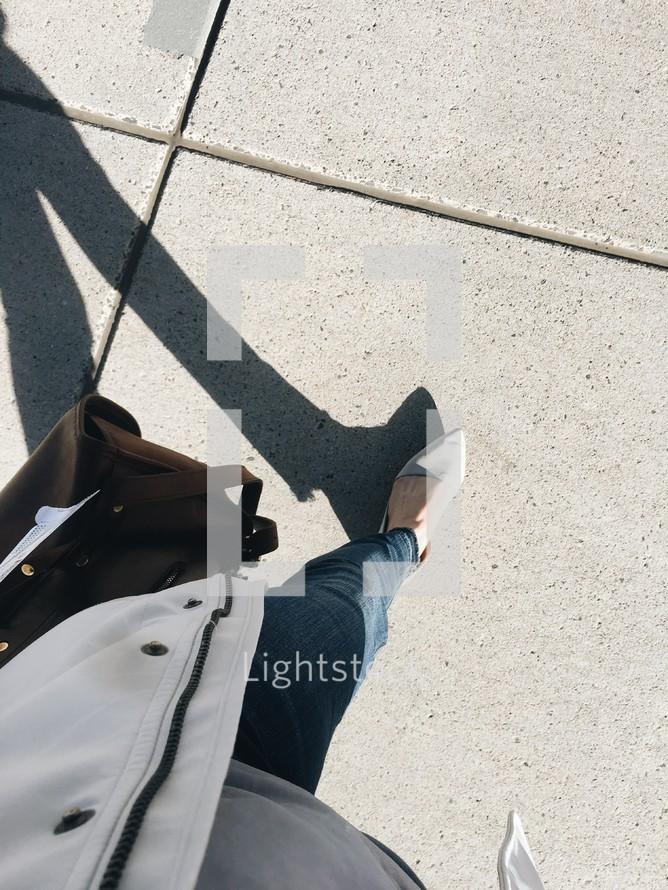 a woman walking on a sidewalk