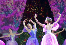 A group of Ballerinas dance in front of a Christmas tree on stage during a performance of The Nutcracker during a Christmas celebration surrounded by Christmas lights and purple and violet lighting.