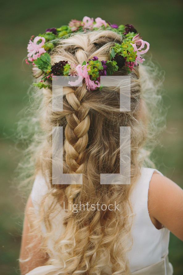 crown of flowers and berries in the hair of a flower girl