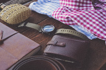 journal, wallet, leather, belt, flask, folded shirts, shirts, watch, travel, packing, trip, table, men's items, father's day