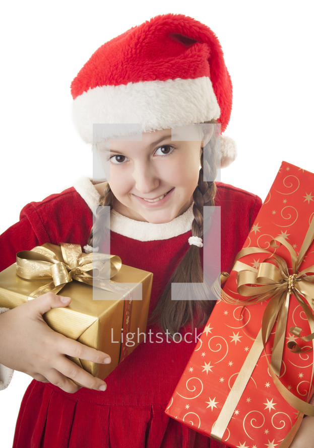 girl child in a santa hat and pigtails holding Christmas gifts
