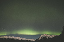 Aurora Borealis over a snow capped mountain peaks in Alaska
