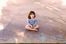 a child sitting on concrete next to chalk drawings