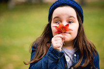 a little girl holding a fall leaf in front of her face