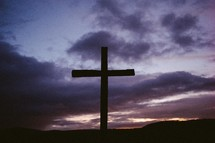 Silhouette of a wooden cross at nightfall.