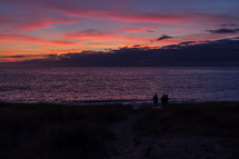 Colorful sunset in early autumn on a Normandy beach in France with three people in silhouette in the foreground