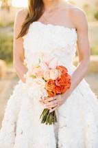 torso of a bride holding a bouquet