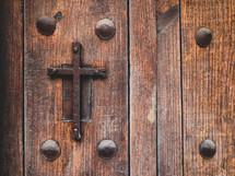 metal cross on a wood church doors