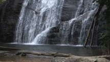 a man sitting and watching a waterfall