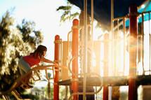 a little girl climbing up playground equipment