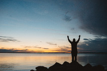 silhouette of a man with raised hands standing by a lake at sunset