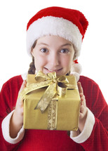 girl child in pigtails and Santa hat holding a Christmas present