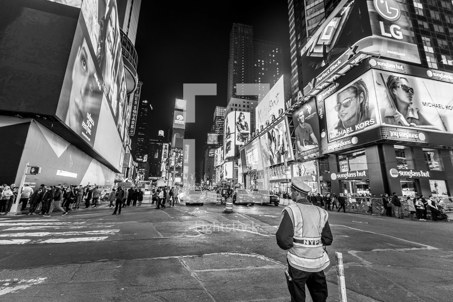 crowds of people on a sidewalk at night in New York City