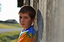 boy child leaning against a barn