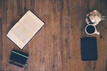 open Bible, journal, pen, coffee pot, iPad, and coffee mug on a wood table