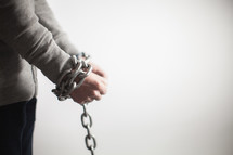 Wrists bound with chain.