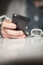 Wrists bound with chain holding a cell phone.