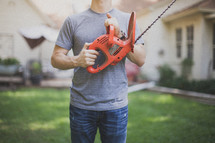 man holding a hedge trimmer