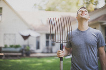 man holding a rake and looking up to God