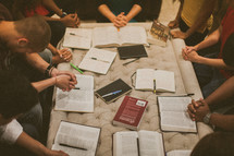 praying hands over Bibles at a Bible study