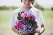 Girl holding a bouquet of flowers.