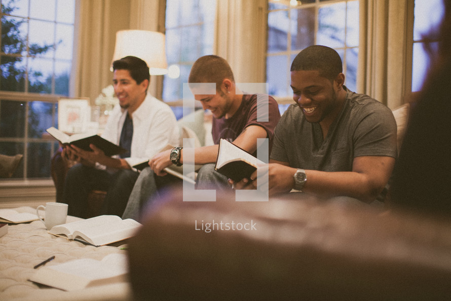 men on the couch reading Bibles at a bible study