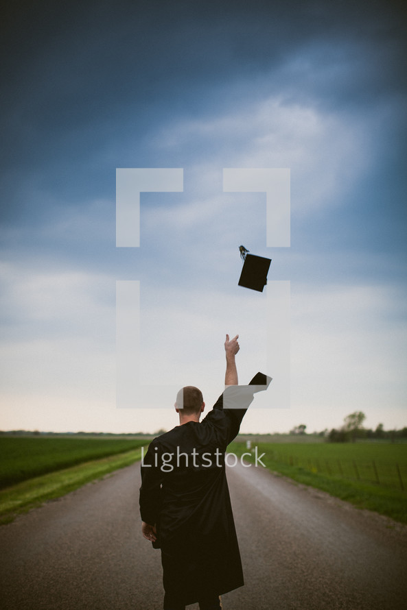 Graduate tossing cap while standing in the middle of the road.