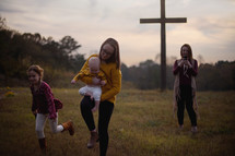 a mother taking pictures of her daughters running in a meadow near a cross