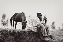 Smiling boy sitting on dirt mound in field with trees holding rope tied to horse.