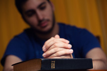 a man with praying hands over a Bible