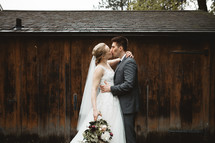 bride and groom kissing in front of a barn