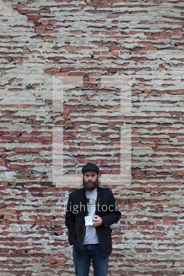 Bearded man with a cup of coffee standing in front of a brick wall.