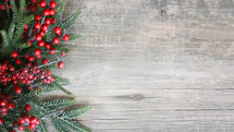 Christmas Holiday Season Background with Red Berries and Greenery Over Wood