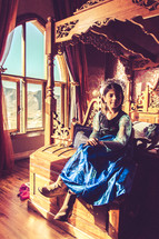 a girl sitting on a bed in a castle dressed up like a princess
