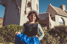 a girl dressed up as a princess in front of Claren's castle