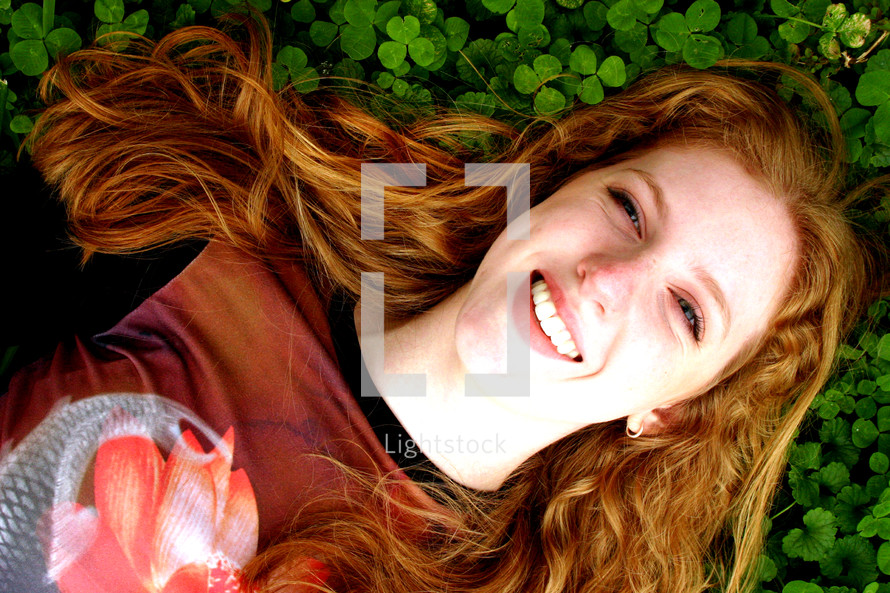 Happy woman lying in clover