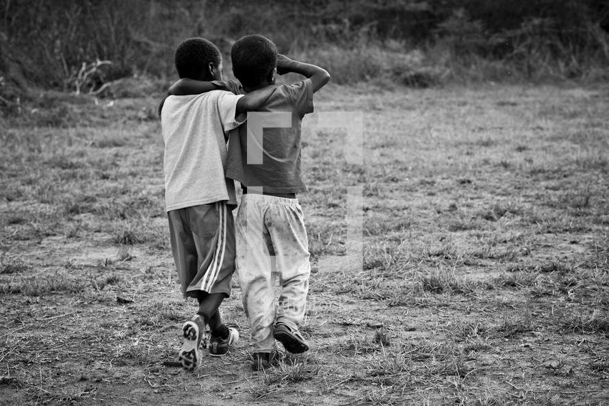Two young boys with their arms around each other as they walk