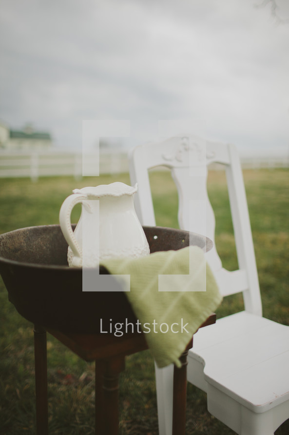 washing basin and pitcher and a white chair for a wedding feet washing ceremony