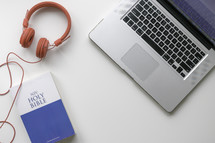 headphones, Bible, and laptop on a desk