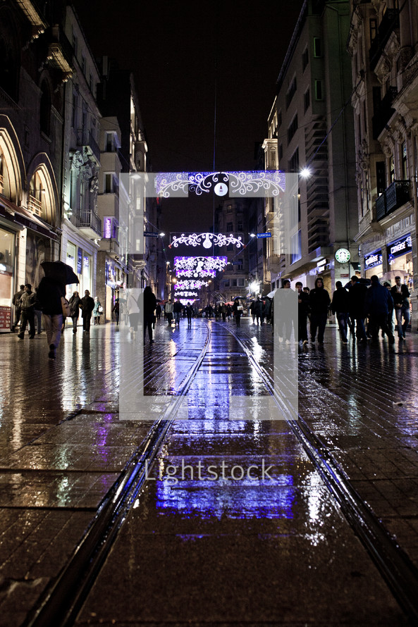 People walk beside trolly tracks on a dark, wet night in Turkey