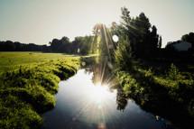 sunburst over a still stream